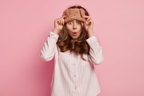 Astonished dark haired young cute European woman has eyemask on forehead, wears pajams, wonders to have dreadful dreams, poses against pink background. People, bed time and surprisement concept.